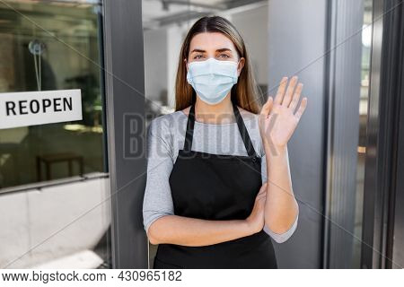 small business, reopening and service concept - woman in mask with reopen banner on window or door glass waving hand