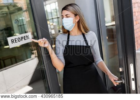 small business, reopening and service concept - woman in mask showing reopen banner on window or door glass