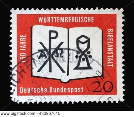 ZAGREB, CROATIA - JUNE 27, 2014: Stamp printed in Germany showing an open Bible with a monogram of Christ and a chalice. 150 years of the Württemberg Bible Institute, circa 1962