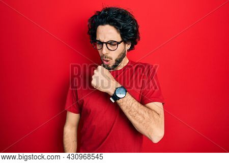 Handsome hispanic man wearing casual t shirt and glasses feeling unwell and coughing as symptom for cold or bronchitis. health care concept.