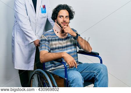 Handsome hispanic man sitting on wheelchair wearing neck collar with hand on chin thinking about question, pensive expression. smiling with thoughtful face. doubt concept.