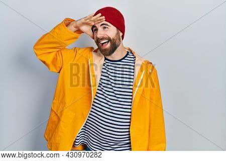 Caucasian man with beard wearing yellow raincoat very happy and smiling looking far away with hand over head. searching concept.