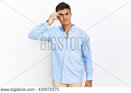 Young hispanic man wearing business shirt standing over isolated background pointing unhappy to pimple on forehead, ugly infection of blackhead. acne and skin problem