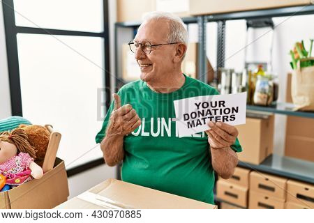 Senior volunteer man holding your donation matters pointing thumb up to the side smiling happy with open mouth