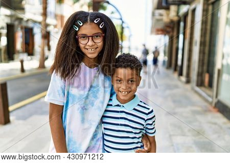 African american family of bother and sister standing at the street looking positive and happy standing and smiling with a confident smile showing teeth