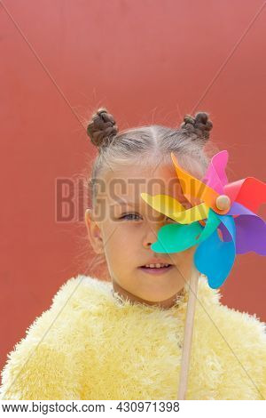 Portrait Of Caucasian Little Girl Of Five Years Old Looking At Camera Holding Pinwheel On One Eye