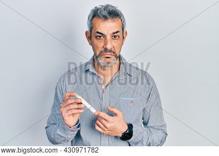 Handsome middle age man with grey hair holding glucometer device depressed and worry for distress, crying angry and afraid. sad expression.
