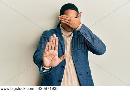 Young handsome hispanic man wearing elegant clothes and glasses covering eyes with hands and doing stop gesture with sad and fear expression. embarrassed and negative concept.