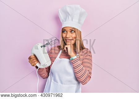 Beautiful hispanic woman holding pastry blender electric mixer with hand on chin thinking about question, pensive expression. smiling and thoughtful face. doubt concept.