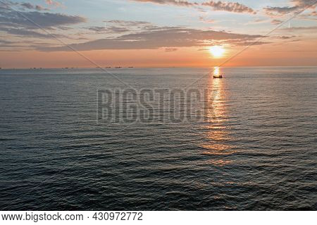 Aerial from a fishing boat on the North Sea and freighters at the horizon at sunset in the Netherlands