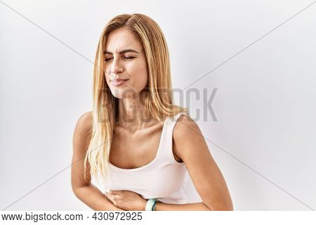 Blonde beautiful young woman standing over white isolated background with hand on stomach because indigestion, painful illness feeling unwell. ache concept.