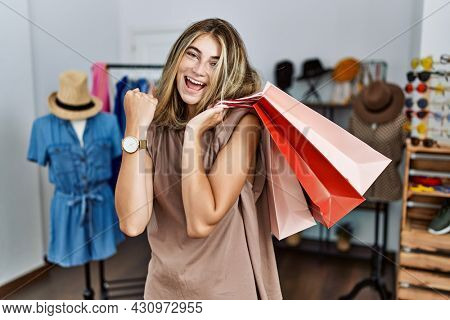 Young blonde woman holding shopping bags at retail shop very happy and excited doing winner gesture with arms raised, smiling and screaming for success. celebration concept.