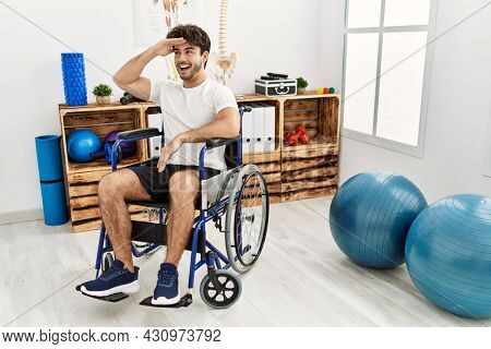Hispanic man sitting on wheelchair at physiotherapy clinic very happy and smiling looking far away with hand over head. searching concept.