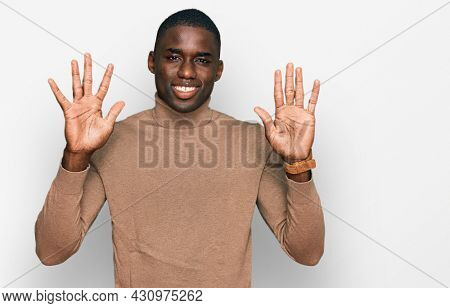 Young african american man wearing casual winter sweater showing and pointing up with fingers number ten while smiling confident and happy.