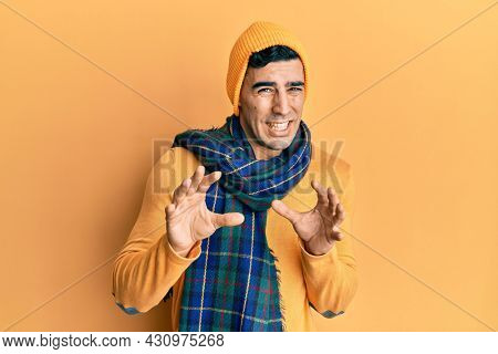 Handsome hispanic man wearing wool hat and winter scarf disgusted expression, displeased and fearful doing disgust face because aversion reaction. with hands raised