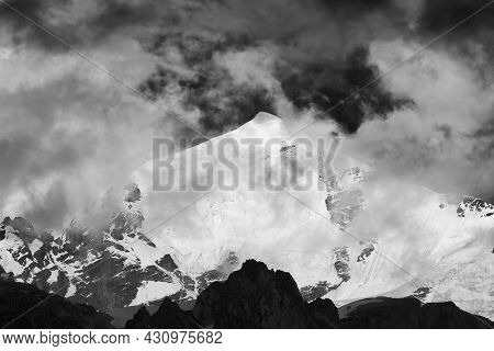 Black And White High Snowy Mountains With Glacier, Rocks And Sky With Dark Fog Before Storm. Caucasu