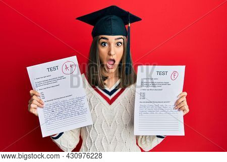 Young brunette girl wearing graduation cap showing exams afraid and shocked with surprise and amazed expression, fear and excited face.