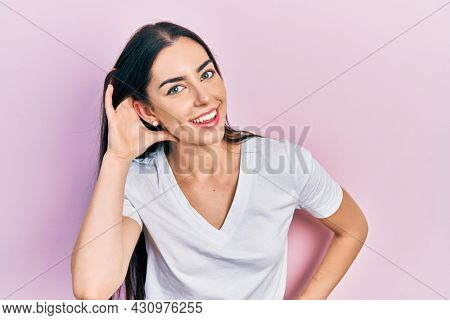 Beautiful woman with blue eyes wearing casual white t shirt smiling with hand over ear listening and hearing to rumor or gossip. deafness concept.