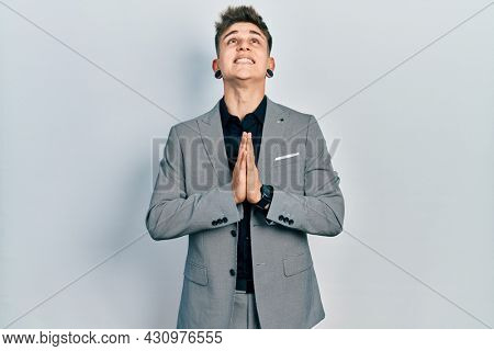 Young caucasian boy with ears dilation wearing business jacket begging and praying with hands together with hope expression on face very emotional and worried. begging.