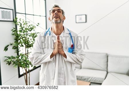 Middle age hispanic man wearing doctor uniform and stethoscope at waiting room begging and praying with hands together with hope expression on face very emotional and worried. begging.