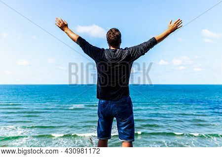 Caucasian Man Spreading Arms And Watching The Ocean. Happy Man With Outstretched Arms.man With His A