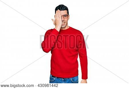 Handsome hispanic man wearing casual clothes and glasses covering one eye with hand, confident smile on face and surprise emotion.