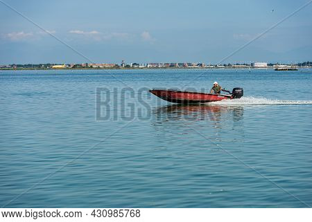 Venice, Italy - June 2, 2021: Small Red Speed Boat With One Person On Board Moving In The Venetian L