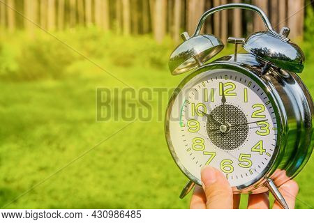 A Woman's Hand Holds An Alarm Clock On A Background Of Forest And Green Grass. Daylight Saving Time