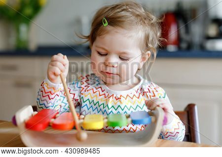 Adorable Cute Beautiful Little Baby Girl Playing With Educational Wooden Music Toy At Home. Happy Ex