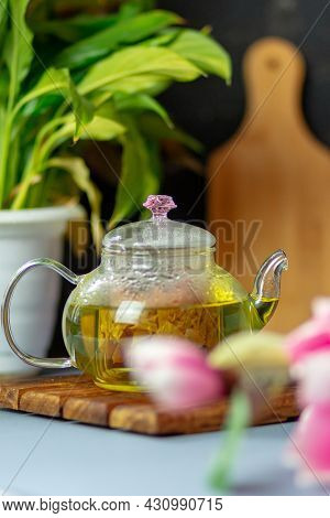 Green Tea With Rose Petals In A Transparent Teapot On A Wooden Table On A Black Background. The Back