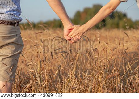 Love Concept. A Couple Holding Hand During Sunset, A Symbol Of Love And Happy Relationship. A Young