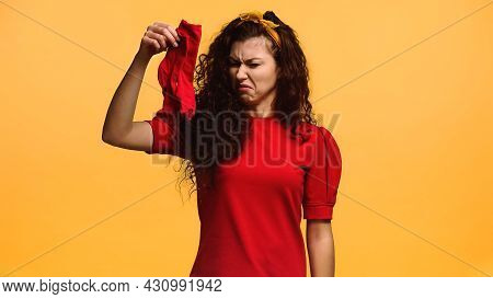 Disgusted Woman Holding Smelly Socks Isolated On Orange