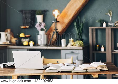 Open Textbook With Pen, Laptop, Stack Of Uncovered Books Lying On Each Other, Cup Of Coffee On Woode