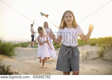 Happy Family With Parents And Kids Playing Together With Snakes On A Beach Vacation. Summer Happines