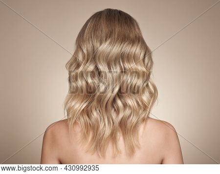 Blonde Woman With Long And Shiny Curly Hair. Beautiful Model Girl With Curly Hairstyle. Care And Bea