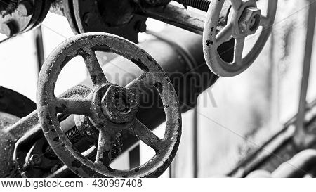 Two Old Grunge Steampunk Valve Wheels Selective Focus With Handle Grip Over Out Of Focus Industrial