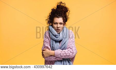 Dissatisfied Woman Freezing In Knitted Sweater And Scarf Isolated On Orange