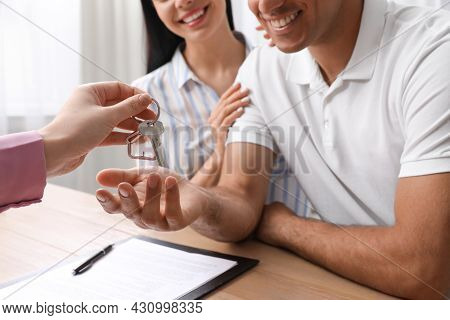 Real Estate Agent Giving House Key To Couple At Table In Office, Closeup