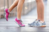 Love sport concept - running couple kissing. Closeup of running shoes and girl standing on toes to kiss boyfriend during jogging workout training outdoors on brooklyn bridge, New York City. poster