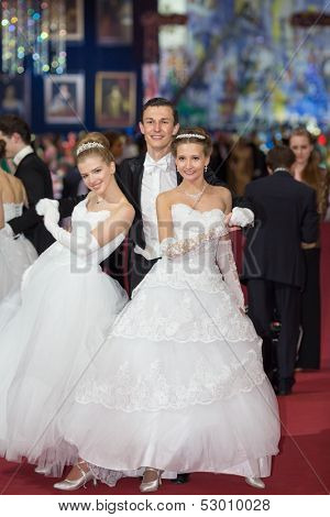 MOSCOW - MAY 25: Two smiling girls in white elegant dress and man in tuxedo at 11th Viennese Ball in Gostiny Dvor on May 25, 2013 in Moscow, Russia.