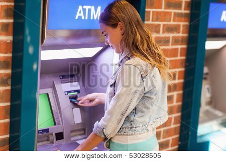 Pretty brunette student withdrawing cash at an ATM