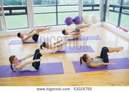 Class stretching on mats at yoga class in fitness studio