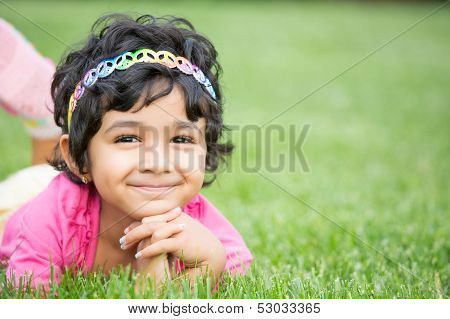 Portrait Of A Smiling Child On Green Grass