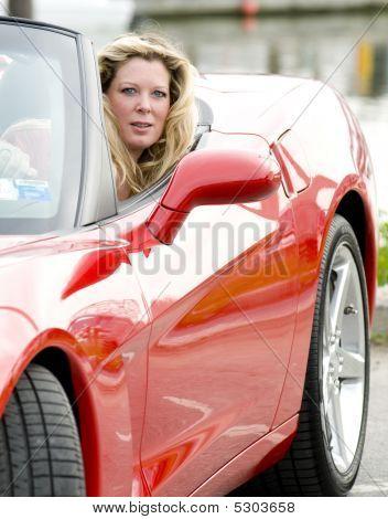 sexy Frau im roten Sportwagen