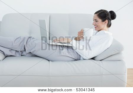Side view of a well dressed young woman with laptop and coffee cup on sofa at home