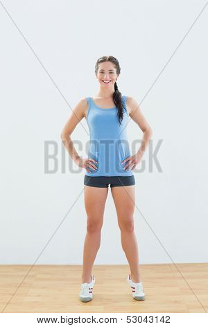 Full length portrait of a slim sporty young woman tip toeing