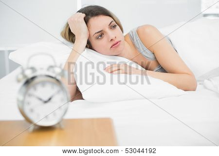 Cute young woman lying exhausted in her bed at home