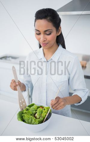 Lovely peaceful woman preparing salad in kitchen at home poster