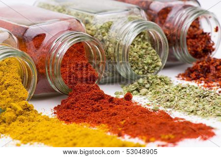 Spice pouring out of set of spice jars close up