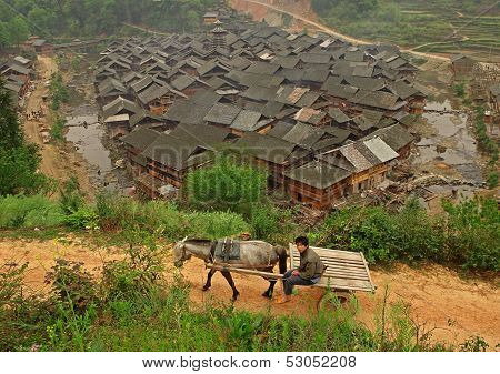 Horse Pulling Cart With Farmer, Against Background Of Chinese Village.